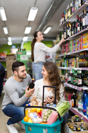 near beer: Beautiful couple squatting in a supermarket near their basket full of food in alcohol section of a shop choosing wine and beer for the evening