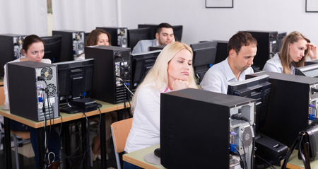 harassing: Russian staff sitting at desks and looking at PC screens Stock Photo