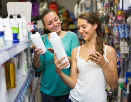 champú: Mujer sonriente joven de elegir el champú en el supermercado Foto de archivo