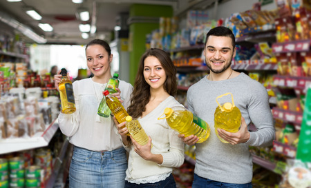 unrefined: Smiling adults holding seed-oil in plastic packing at shop. Selective focus Stock Photo