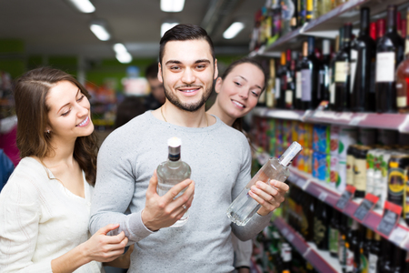 liquor girl: Smiling young adults with bottles of vodka at supermarket. Focus on guy