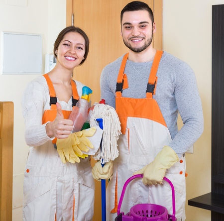 houseman: Portrait of professional cleaners with equipment at door of client house Stock Photo