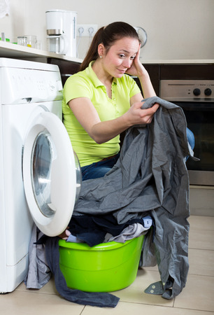 dirty clothes: Unhappy young girl with dirty clothes near washing machine