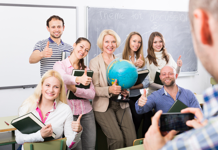 25s: Happy professionals and coach making group portrait at a school Stock Photo