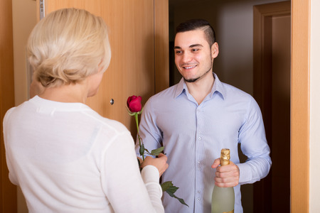 liaison: Aged woman meeting smiling young boyfriend with flowers and wine in hands at doorway Stock Photo