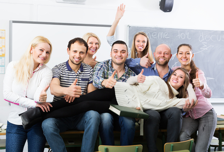 cohesive: Portrait of friendly teacher and adult happy students in classroom