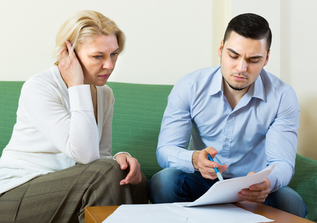 Upset mature woman questioning young man about letters from bank at home Stock Photo