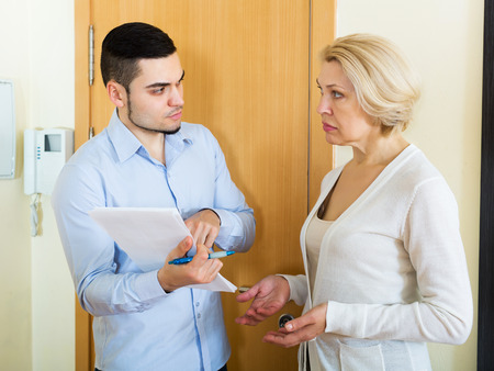 Ð¡ollector is trying to get the arrears from woman at home door Stock Photo