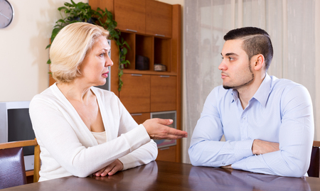adult intercourse: Sad man and his mature girlfriend having serious conversation indoors Stock Photo