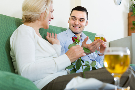 Smiling adult son congratulating happy senior mother and proposing a toast