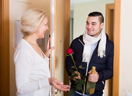 Smiling handsome man and elderly woman standing at doorway Stock Photo