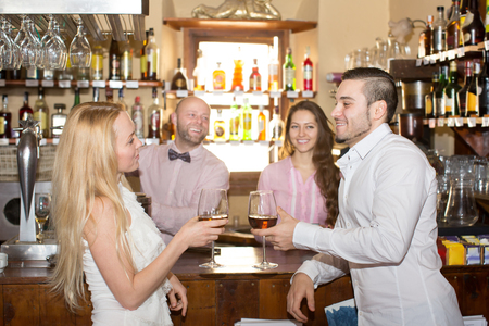 entertaining: Happy bartender entertaining guests at a bar counter
