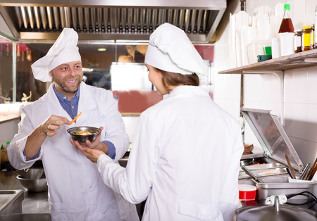 house robes: Happy cooks cooking at professional kitchen in the take-away  restaurant