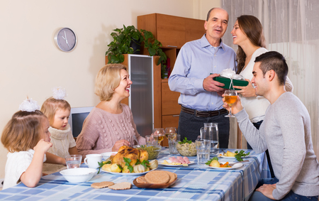 congratulating: Young smiling girl congratulating heartily family member at the table at home Stock Photo