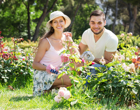 floriculturist: Young happy couple is engaged in gardening together
