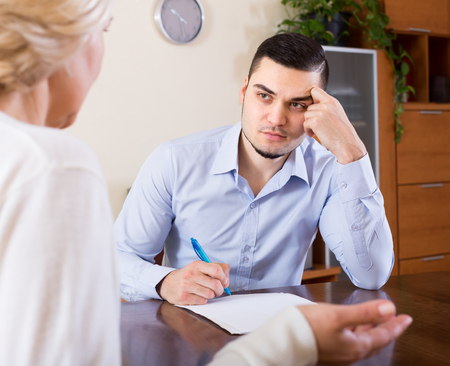 Upset senior mature woman questioning young man about letters from bank at home