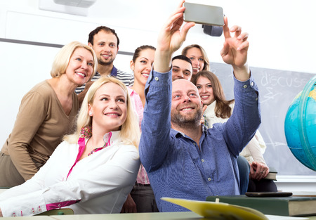 pose: Smiling students posing in a classroom while their lecturer is taking a group selfie with his phone Stock Photo