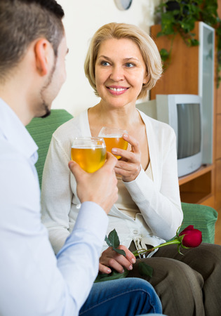 mismatch: Happy smiling aged woman with young boyfriend drinking wine at home Stock Photo