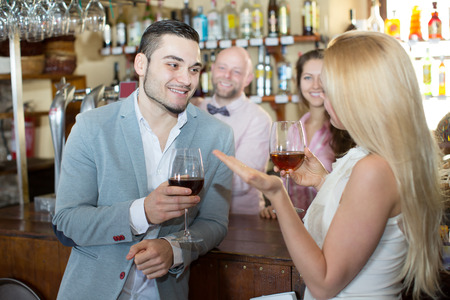 entertaining: Positive happy bartender entertaining guests at bar counter in bar Stock Photo