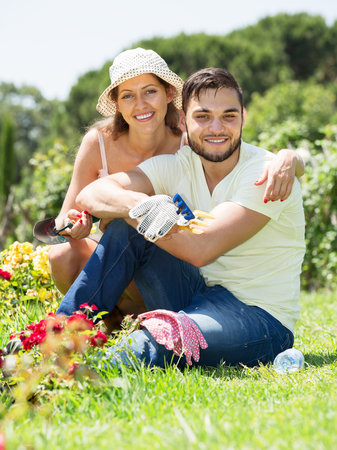 floriculturist: Young happy family with gardening tool in their backyard garden