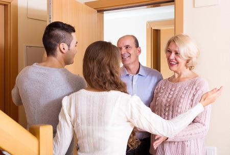 invitando: familia joven invitando a los padres de edad avanzada que venir dentro Foto de archivo