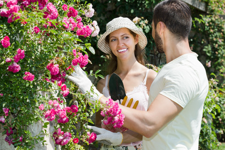 sundry: Happy family in garden flowers with horticultural sundry for planting Stock Photo