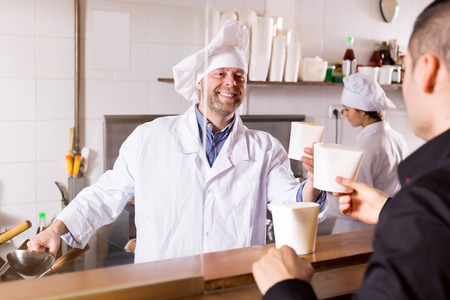 cook house: Smiling cook and client buying take-away food at eating house Stock Photo