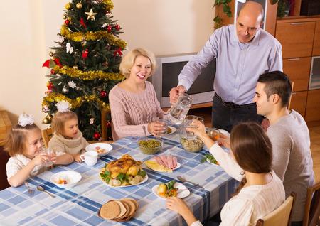 familia unida: Familia unida en la mesa festiva cerca del �rbol de Navidad
