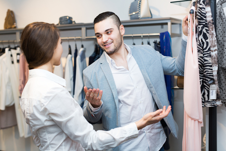 shop assistant: Positive customer consulting with female shop assistant