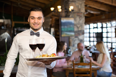 respectful: Cheerful adults people having dinner and respectful waiter