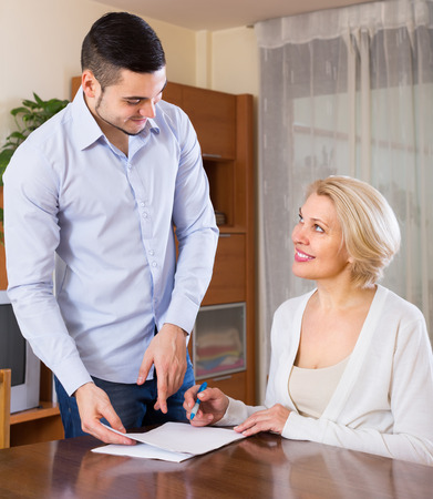 mismatch: Smiling young man and aged woman sitting with banking documents indoors