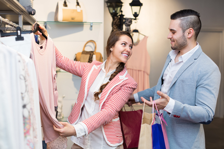 shoppingbag: Portrait of happy smiling young couple choosing new apparel in store