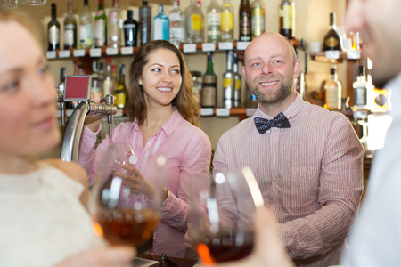 entertaining: Positive happy bartender entertaining guests at a bar counter