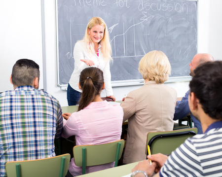 Professional business coach speaking up in front of attentive students Stock Photo