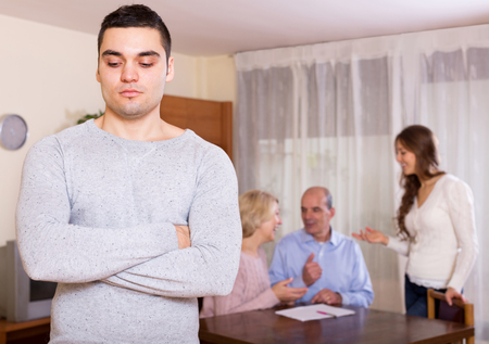 hypothec: Upset young man staying against united family members
