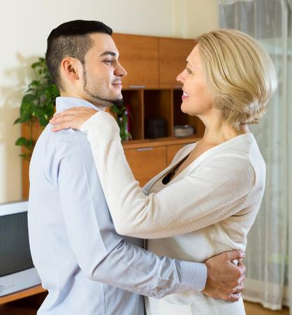gigolo: Young smiling man and senior woman slowly dancing at home