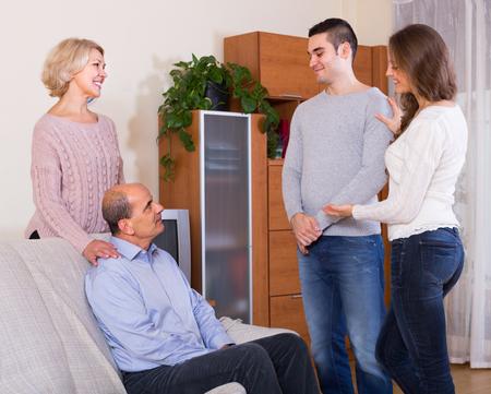 introducing: Happy adult daughter introducing her boyfriend to her parents indoor