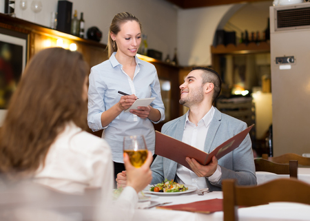restaurant interior: Young blonde waitress offering tasty dishes to smiling guests couple. Selective focus