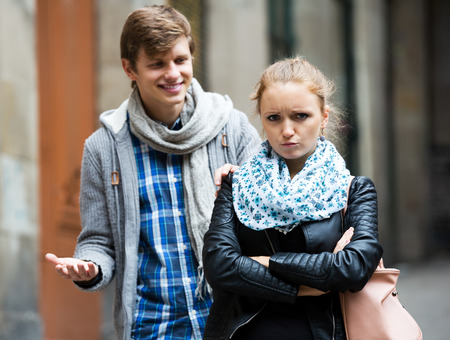 accosting: Pretty blonde cannot get rid off bothering admirer outdoors. Focus on the woman