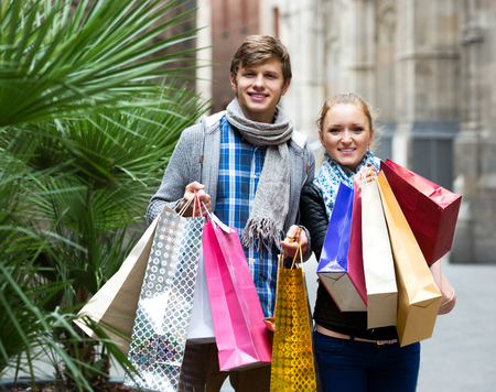 the spouse: Attractive young spouse walking through European town and carrying shopping bags Stock Photo