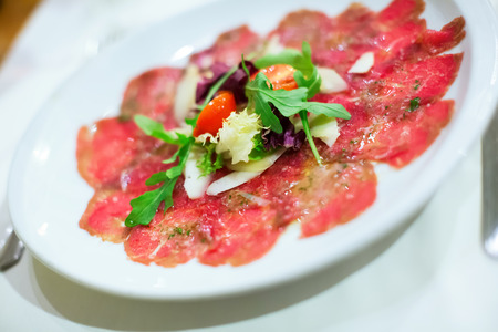thinly: Thinly sliced appetizer meat carpaccio served with rocket salad Stock Photo