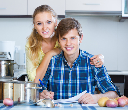 middle joint: positive spanish spouses signing documents and smiling at kitchen Stock Photo