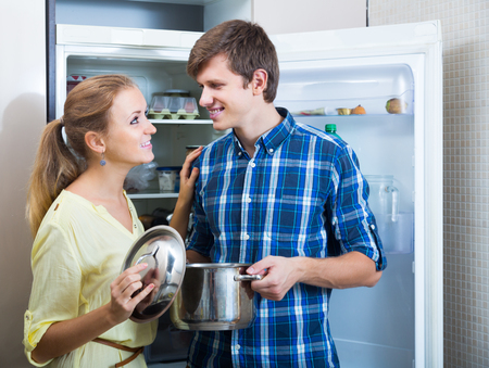 kitchen spanish: happy spanish  young man and woman standing near fridge in kitchen Stock Photo
