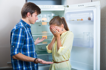 Portrait of poor and hungry couple near empty fridge 스톡 콘텐츠