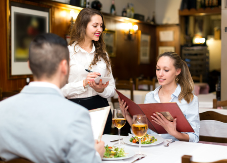 Positive waitress taking table order and smiling at tavern Reklamní fotografie