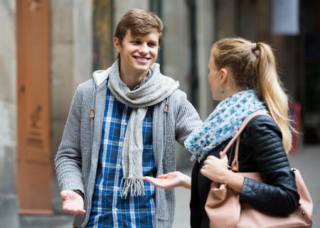 Hezký mladý americký muž student honí potěšený dívka na venkovní dni. zaměřit se na chlapce Reklamní fotografie