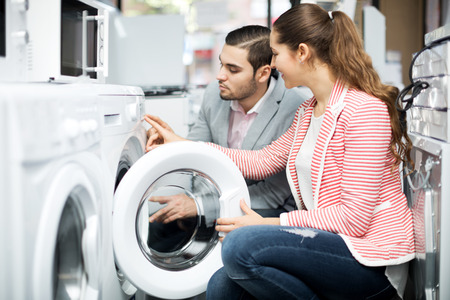 lavadora con ropa: Attractive young family couple buying new clothes washer in supermarket. Focus on the woman