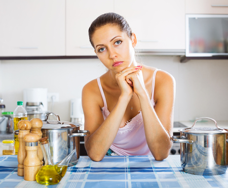 leaning on elbows: Pensive young woman leaning her elbows at the kitchen Stock Photo