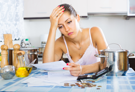 in low spirits: Tired and sad young woman reading bills at the kitchen
