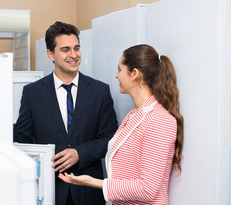 domestic appliances: Satisfied smiling customers looking at large fridges in domestic appliances section